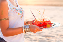 Woman holds a dish with a drinks at sunset. Picnic theme Stock Photo