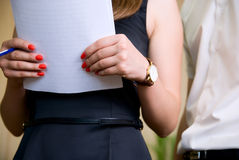 Woman holds document and man nearby Stock Images