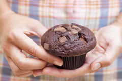 Woman holds Double chocolate chip muffin in her hands Royalty Free Stock Photos