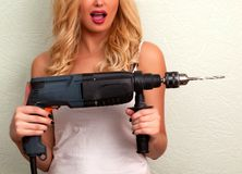 Woman holds a drill. Surprised woman holds a drill Stock Images
