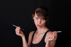 Woman holds electric and ordinary cigarette Stock Image