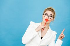 Woman holds fake lips on stick pointing at copy space Stock Photography