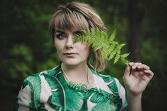 Woman holds a fern in her hand. royalty free stock images