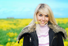 Woman holds a flower in teeth. Young beautiful woman holds in  teeth a yellow floret against meadow and the sky Stock Image