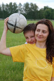 Woman holds football, boy peeps out Royalty Free Stock Images
