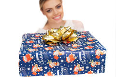 Woman holds a gift wrapped in christmas paper Stock Image