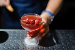 Woman holds a glass with an alcoholic cocktail decorated with three cherries Royalty Free Stock Image