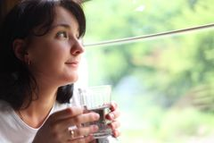 Woman Holds Glass Andlooks In Train`s Window Stock Photo