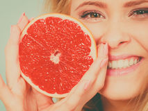 Woman holds grapefruit citrus fruit in hands. Woman positive girl holding half of red grapefruit citrus fruit in hands near mouth. Healthy diet food. Summer Stock Photography