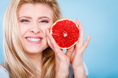 Woman holds grapefruit citrus fruit in hands. Woman smiling blonde girl holding half of red grapefruit citrus fruit in hands near mouth., on blue. Healthy diet Royalty Free Stock Photo