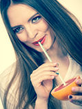 Woman holds grapefruit drinking juice from fruit Stock Images
