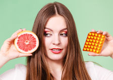 Woman holds grapefruit and pills blister pack vitamin c Stock Photography