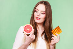 Woman holds grapefruit and pills blister pack vitamin c Royalty Free Stock Photography