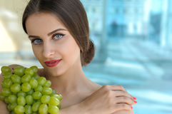Woman holds grapes in the chest and hugs it. With both hands. Beauty portrait with bare shoulders and her hair gathered against the glass background Royalty Free Stock Photo