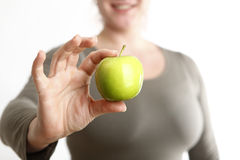 Woman holds a green apple into to camera Royalty Free Stock Images