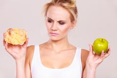 Woman holds cake and fruit in hand choosing Stock Photos