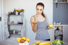 Woman holds in hand cake sweet bun and apple fruit choosing, trying to resist temptation, make the right dietary choice. Weight lo. Ss diet dilemma gluttony Stock Photos