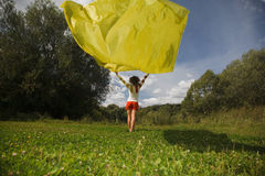 Woman holds in hand developing on wind fabric. Young woman in sunny summer day holds in hand developing on a wind a yellow fabric Stock Image