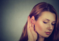 Woman holds hand near ear and listens carefully Royalty Free Stock Photography