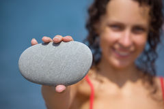 Woman holds in hand pebble, focus on pebble Stock Photo
