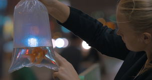 Woman holds in hand plastic package with aquarium gold fish in the shopping mall. Hong Kong, China stock video footage