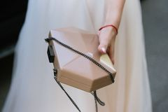 Woman holds in hand a small female handbag royalty free stock images