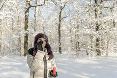 A woman holds a handful of snow in her hands and blows on it. Wi. Nter in the forest. The sun sparkles Stock Photo
