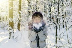 A woman holds a handful of snow in her hands and blows on it. Wi royalty free stock photo