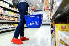 A woman holds the handle of the grocery cart, going down the aisle in the supermarket. Buy the product. Saint-Petersburg. Russia. royalty free stock images