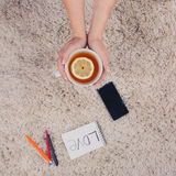 A woman holds hands a cup of tea with lemon, phone, pen and notebook lying on the carpet, top view. A woman holds hands a cup of tea with lemon, phone, pen and Royalty Free Stock Photos