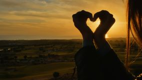 Female hands in form of heart against sunset. Woman holds hands in form of heart and moves them against the sunset. Bright sun inside the heart. Close-up stock video footage