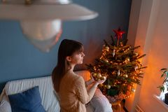 Woman holds in the hands of Golden Christmas tree toys. Winter holidays in a house interior. Golden and white Christmas. Happy young woman decorating christmas royalty free stock photos