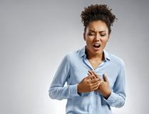 Woman holds hands on painful chest. Photo of african american woman in blue shirt on gray background. Medical concept. Heart attack royalty free stock image