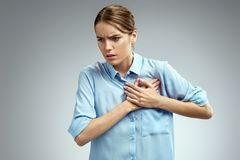 Woman holds hands on painful chest. Photo of american woman in blue shirt on gray background. Medical concept. Heart attack stock photo