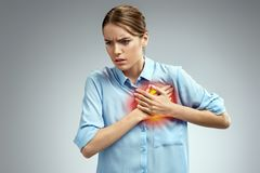 Woman holds hands on painful chest. Photo of american woman in blue shirt on gray background. Medical concept. Heart attack royalty free stock images