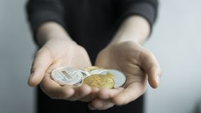 Woman holds in hands physical cryptocurrency coins - golden and silver bitcoins, ethereum and silver litecoin. Profit stock photography