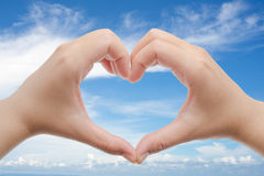 Woman holds hands up to sky in the shape of a heart Royalty Free Stock Image