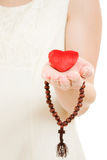 Woman holds the heart and the rosary in his hand Royalty Free Stock Image