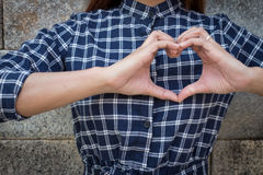 Woman holds heart shape on own Royalty Free Stock Images