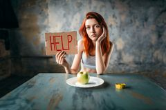 Woman holds help sign against plate with apple. Young woman holds help sign in hand against plate with apple. Weight loss diet concept, fat burning Royalty Free Stock Photo