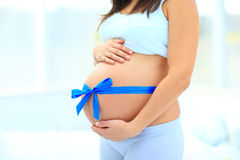 Woman holds her baby bump Royalty Free Stock Images