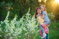 A woman holds her daughter in her arms. A women holds her daughter in her arms and smile Royalty Free Stock Image