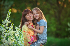 A woman holds her daughter in her arms. A women holds her daughter in her arms and smile Stock Photo