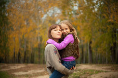 A woman holds her daughter in her arms Stock Images