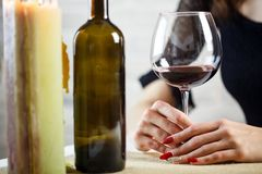 A woman holds in her hand a glass of wine on a blind date. Two wineglass on the table. Close up stock photo