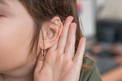Woman holds her hand near ear and listening carefully Stock Photo