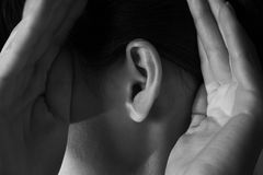 Woman holds her hands near ear Royalty Free Stock Image