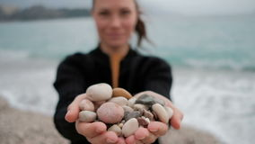 Woman holds in her hands a pile of rocks at the shore with the waves. stock video footage