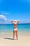 Woman holds her hat down standing on beach Royalty Free Stock Photos