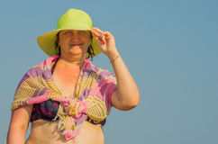 Woman holds her hat in the wind Royalty Free Stock Image